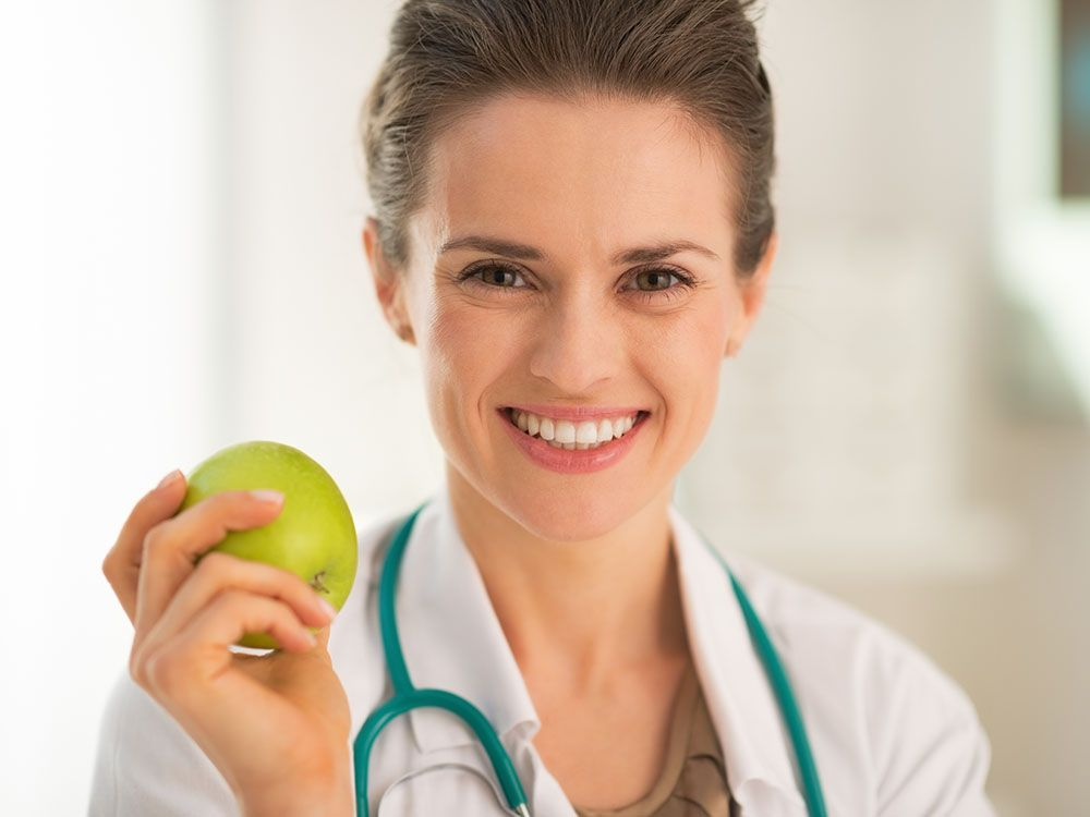 Portrait of smiling medical doctor woman with apple